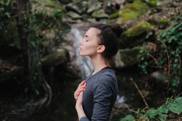 young woman practicing breathing yoga pranayama outdoors in moss forest on background of waterfall. unity with nature concept. - w stanie zen zdjęcia i obrazy z banku zdjęć