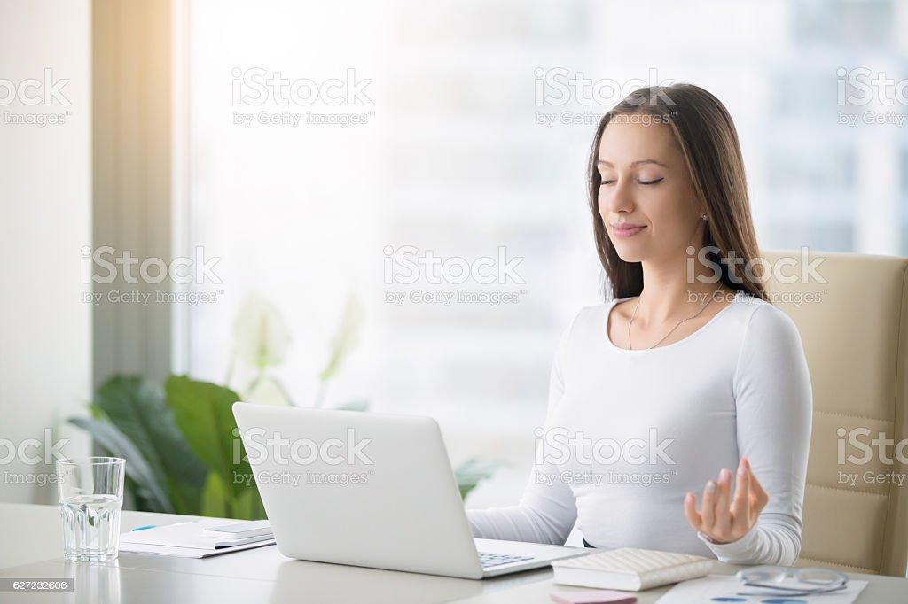 Young woman practicing meditation at the office desk - Lizenzfrei Aktiver Lebensstil Stock-Foto