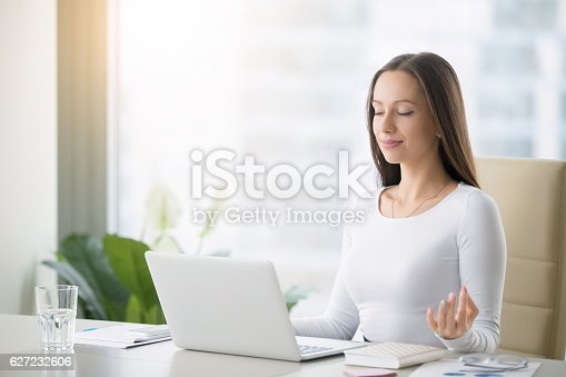 istock Young woman practicing meditation at the office desk 627232606