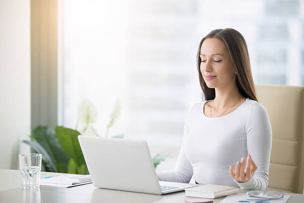 Young woman practicing meditation at the office desk stock photo