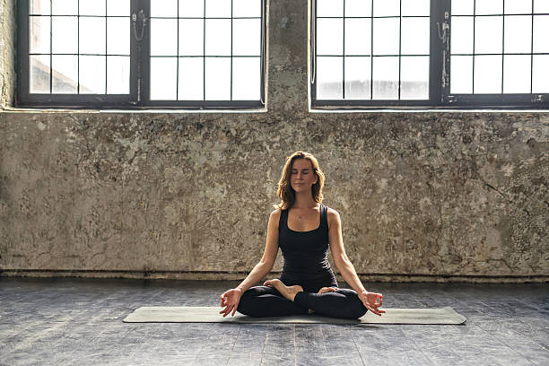 Young woman practicing meditation in a loft studio Young woman practicing meditation in a loft studio lotus position stock pictures, royalty-free photos & images