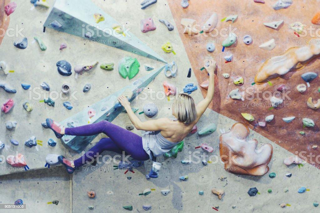 Junge Frau üben Klettern auf einer Felswand im Innenbereich – Foto