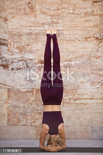 Full length of young woman practicing headstand. Rear view of female athlete is doing yoga. She is wearing sports clothing.