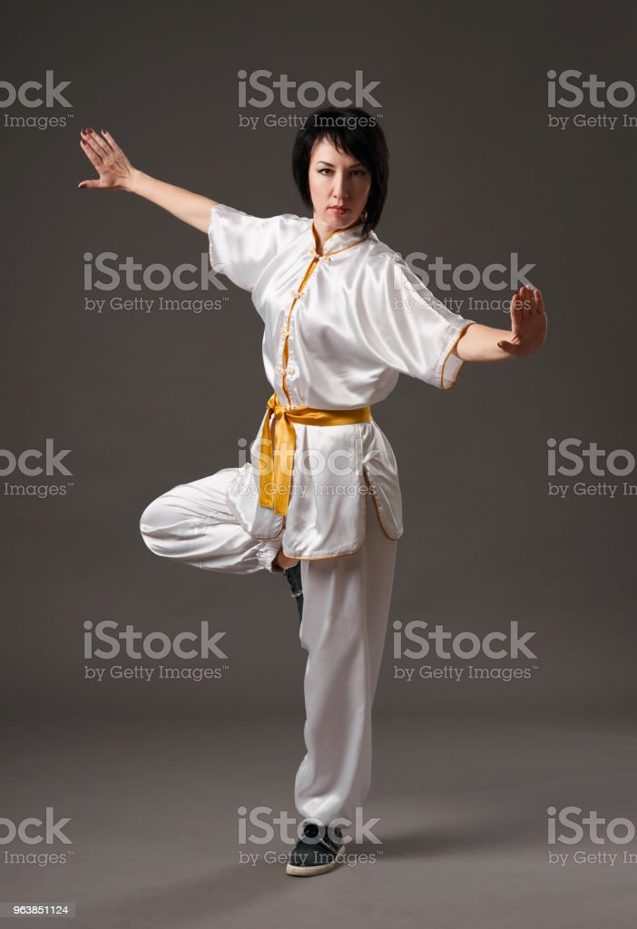 Young woman practicing tai chi chuan. Chinese management skill Qi's energy. Gray background, studio shoot. - Royalty-free Adult Stock Photo