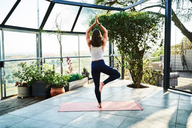 Junge Frau üben Baumpose auf Gymnastikmatte – Foto