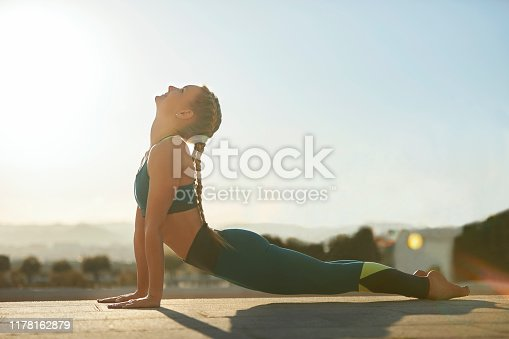 Side view of young woman practicing upward facing dog position at park. Full length of flexible female athlete is doing yoga on footpath. She is exercising on sunny day.