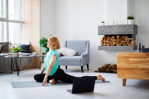 Young woman practicing yoga at home with laptop during quarantine stock photo