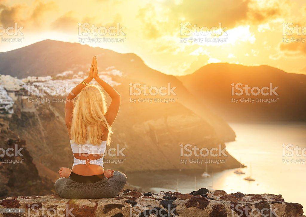 Young woman practicing yoga at sunset in Santorini Greece stock photo