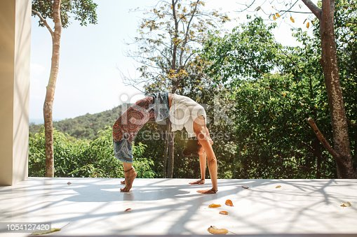 Young woman doing morning yoga exercise at her home terrace in Koh Phangan island in Thailand. She is doing stretching and meditation, relaxing on the beginning of a new day.