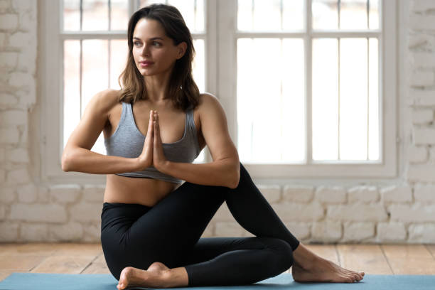 Young woman practicing yoga, doing Ardha Matsyendrasana pose Young attractive woman practicing yoga, doing Half lord of the fishes exercise, Ardha Matsyendrasana pose with namaste , working out, wearing sportswear, pants and top, indoor full length, yoga studio prayer pose yoga stock pictures, royalty-free photos & images