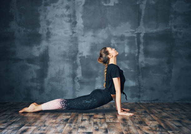 Young woman practicing yoga, doing cobra Pose on dark background Young woman practicing yoga, doing cobra Pose (Bhujangasana) on dark background.  sport and healthy lifestyle cobra pose stock pictures, royalty-free photos & images