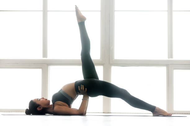 Young woman practicing yoga, doing Eka Pada Setu Bandha Sarvangasana Young sporty attractive woman practicing yoga, doing Eka Pada Setu Bandha Sarvangasana exercise, Glute Bridge pose, working out, wearing sportswear, grey pants, top, indoor full length, at yoga studio shoulder stand stock pictures, royalty-free photos & images