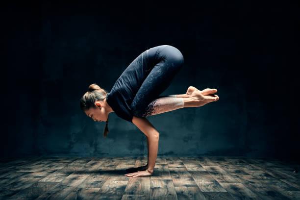 Junge Frau üben Yoga tun Unterarm Stand Krane Pose Asana in dunklen Raum – Foto