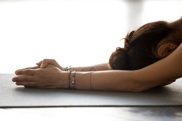 young woman practicing yoga, doing meditation exercise - yin yang symbol stock pictures, royalty-free photos & images