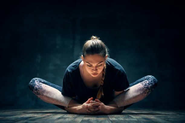 Junge Frau üben Yoga tun gelehnte Göttin Pose Asana in dunklen Raum – Foto