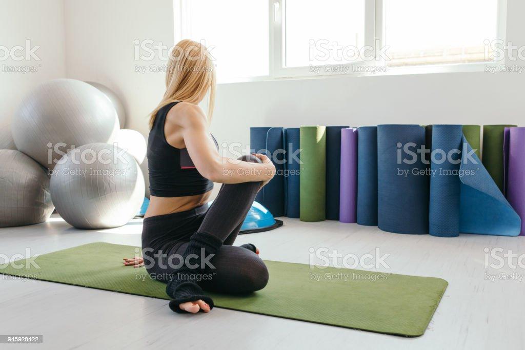 Young Woman Practicing Yoga in a Fitness Studio. Marichyasana. stock photo