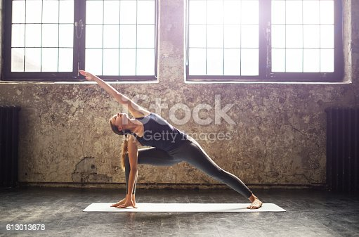 istock Young woman practicing yoga in an urban loft 613013678