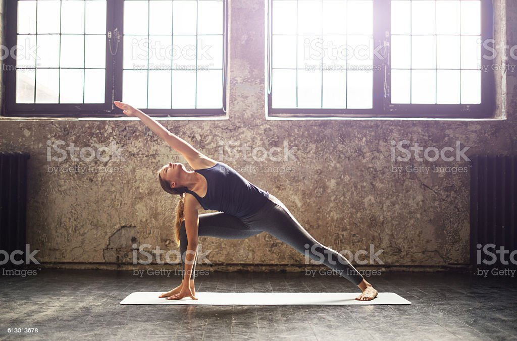 Young woman practicing yoga in an urban loft - foto de stock