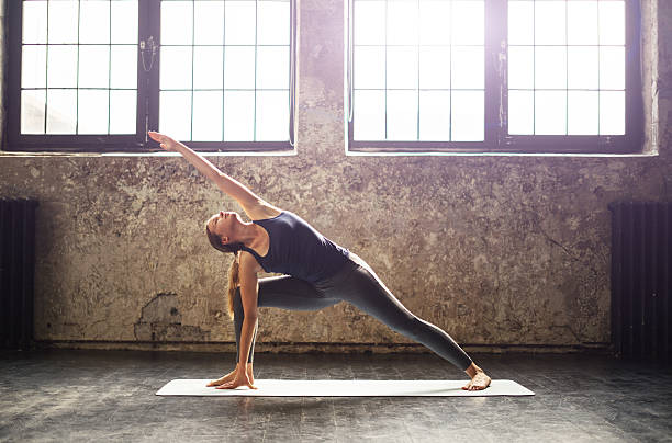young woman practicing yoga in an urban loft - yoga stock photos and pictures