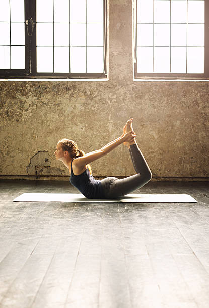 Young woman practicing yoga in an urban loft stock photo