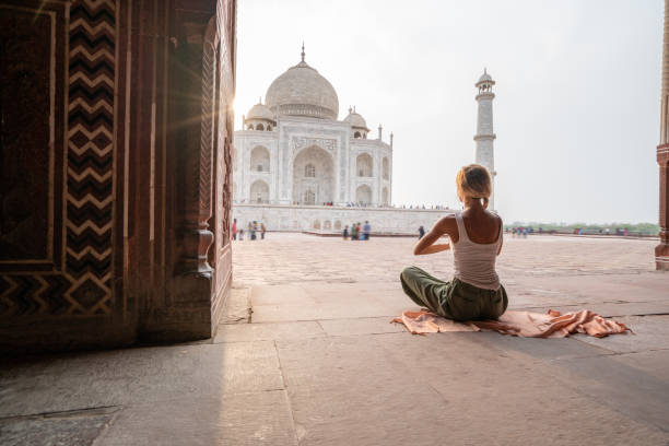 Young woman practicing yoga in India at the famous Taj Mahal at sunrise - Headstand position upside down- People travel spirituality zen like concept stock photo