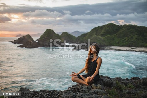 istock Young woman practicing yoga in lotus pose at sunset with beautiful ocean and mountain view. Sensitivity to nature. Self-analysis and soul-searching. Spiritual and emotional concept. 1159495300