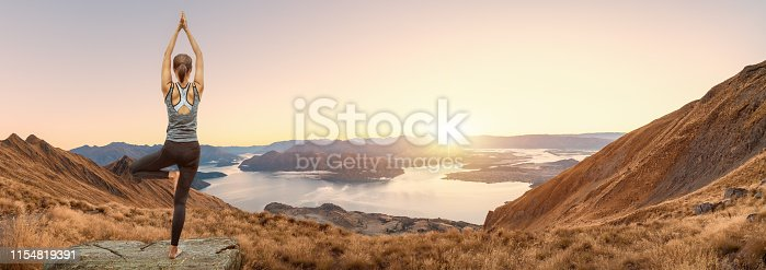 istock Young woman practicing yoga in the nature, Female happiness, Young woman is practicing yoga at mountain. Young woman practicing yoga in roys peak track, New Zealand. 1154819391