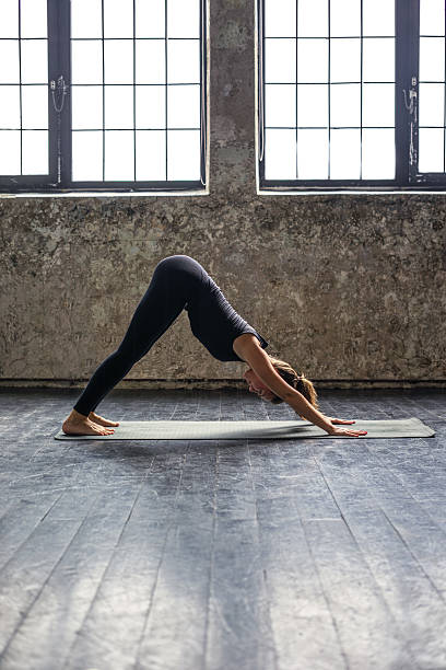 Young woman practicing yoga in urban loft: downward facing dog stock photo