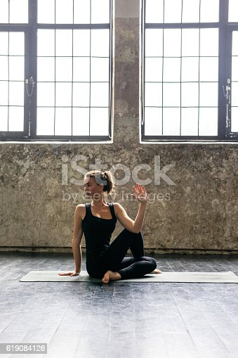 istock Young woman practicing yoga in urban loft: spinal twist pose 619084126