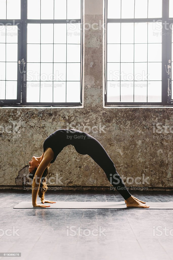 Young woman practicing yoga in urban loft: Upward Bow Pose – Foto