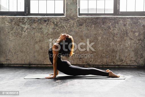 Young woman practicing yoga in an urban studio
