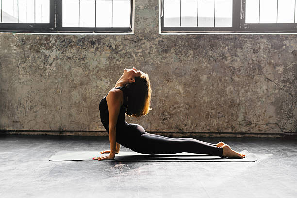 Young woman practicing yoga in urban loft: Upward Facing Dog Young woman practicing yoga in an urban studio upward facing dog position stock pictures, royalty-free photos & images