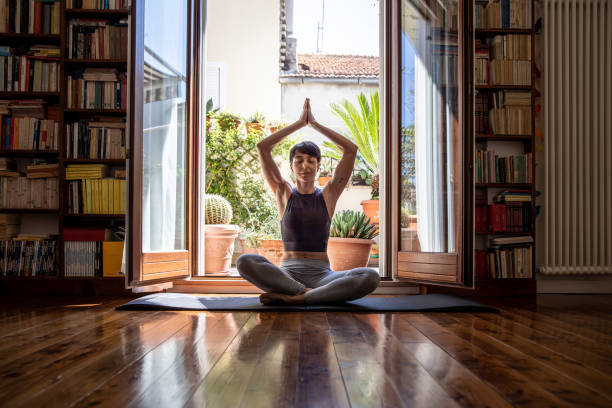Young woman practicing Yoga in video call from home stock photo