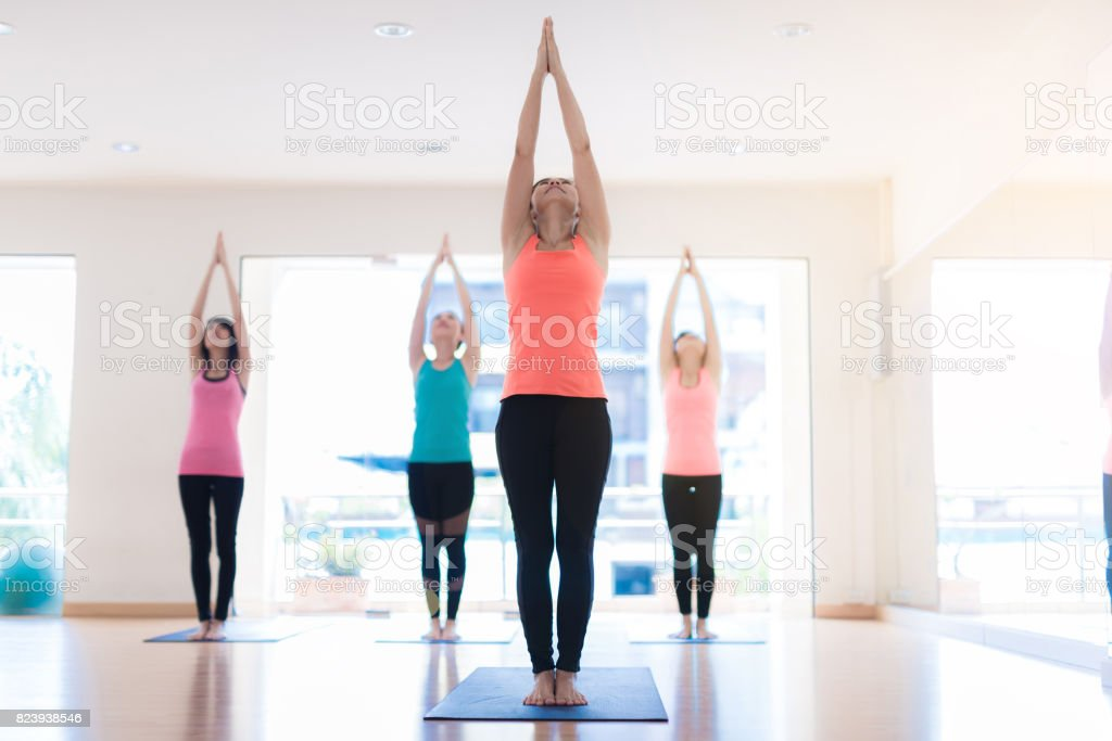 Young woman practicing yoga in yoga class in fitness center stock photo