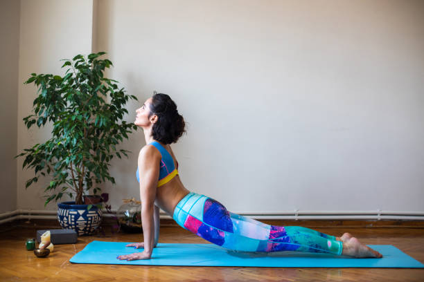 Young woman practicing yoga indoor Young woman practicing yoga indoor upward facing dog position stock pictures, royalty-free photos & images