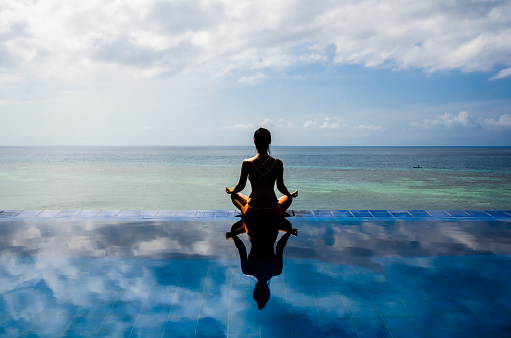 istock Young woman practicing yoga lotus position on the Infinity pool 1129395061