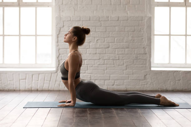 Young woman practicing yoga, lying in Cobra pose, Bhujangasana Young beautiful woman practicing yoga, lying in Cobra pose, doing Bhujangasana exercise, attractive girl in grey sportswear, leggings and bra working out at home or in modern yoga studio cobra pose stock pictures, royalty-free photos & images