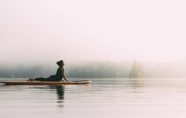 Young Woman Practicing Yoga On A Paddleboard stock photo