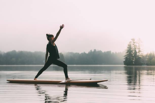 junge frau übt yoga auf einem paddleboard - gleichgewicht stock-fotos und bilder