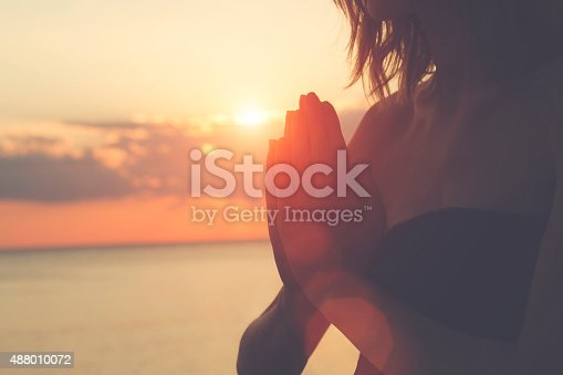 istock Young woman practicing yoga on the beach. 488010072