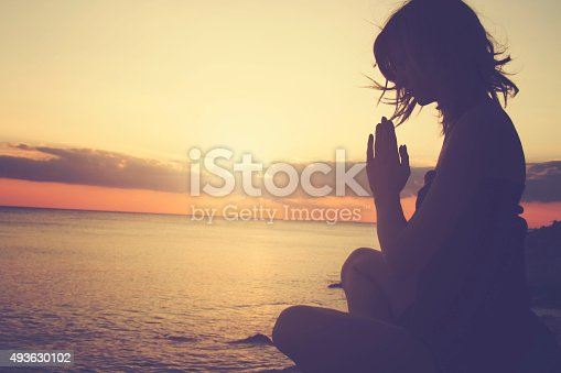 istock Young woman practicing yoga on the beach. 493630102