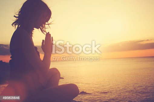 istock Young woman practicing yoga on the beach. 495805646