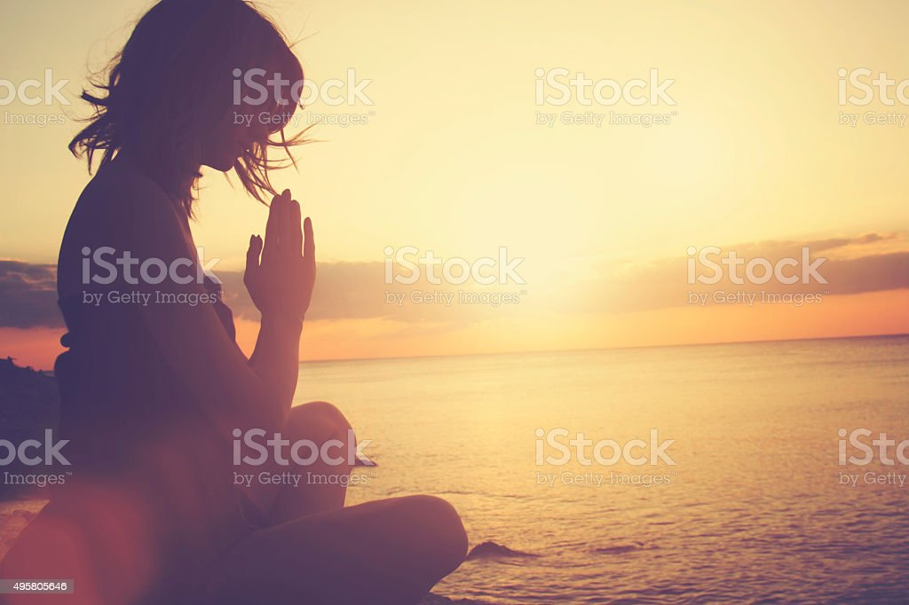 Young woman practicing yoga on the beach. stock photo