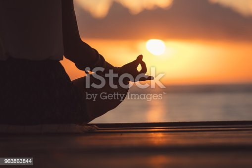 Young woman practicing yoga on the beach.