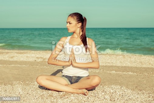 Caucasian young woman practicing yoga or fitness at seashore at sunset