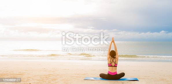Young woman practicing yoga outdoor on the beach in morning