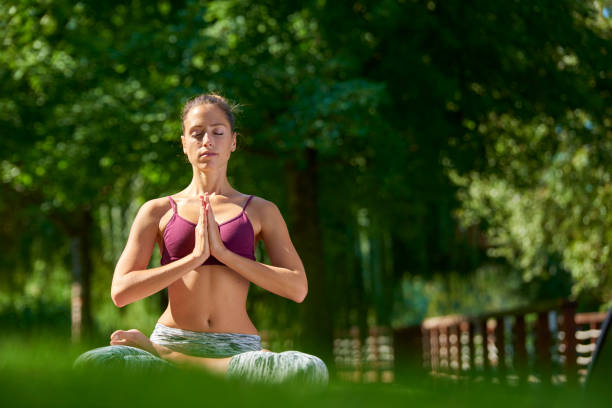 Young woman practicing yoga outdoor Full length shot of a young woman sitting in lotus pose and practicing yoga in the city park. yoga instructor stock pictures, royalty-free photos & images