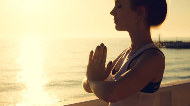 Young woman practicing yoga outdoors by the sea at sunset. Girl standing with eyes closed and prayer hands. Female portrait in profile. stock photo