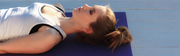 Young woman practicing yoga outdoors. Girl in shavasana on purple mat on white wooden floor. Portrait in profile close up. stock photo