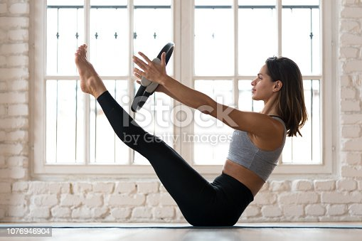 istock Young woman practicing yoga, Paripurna Navasana exercise with a ring 1076946904